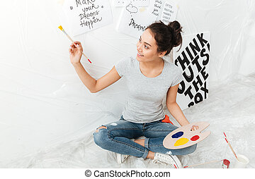 Happy young lady artist sitting on floor over white...