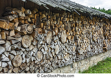 Chopped firewood stacked in a woodpile under a canopy -...