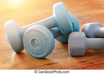Blue dumb-bells on a floor - Blue dumb-bells over wooden...
