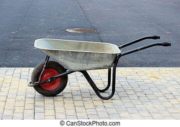 A construction empty wheelbarrow stands on the sidewalk next to an asphalt parking lot for tourist buses during construction.