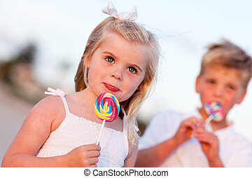 Cute Little Girl and Brother Enjoying Their Lollipops at the...