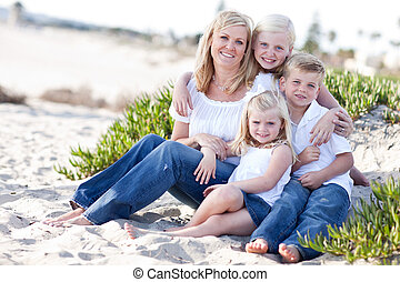 Attractive Mom and Her Cute Children at The Beach