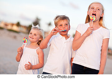 Cute Brother and Sisters Enjoying Their Lollipops Outside -...