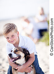 Handsome Young Boy Playing with His Dog at the Beach