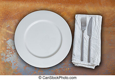 Empty plate with cutlery on rusty steel background