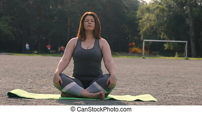 Plus size girl meditating outdoors yoga - Beautiful plus...