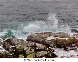 Ocean waves splash against shore rocks in Jamestown Rhode...