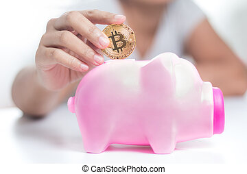 Close up shot hands of woman putting gold bitcoin to pink...