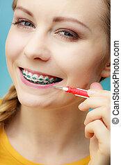 Woman with teeth braces using interdental brush - Dentist...