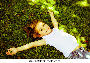 Happy Little Girl Lying On The Grass