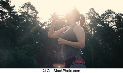 Overweight woman drinking water after workout
