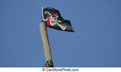 Jolly Roger danger Pirate flag develops against the blue sky...