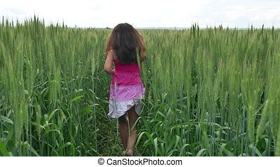 Girl teenager runs along a green field with wheat. happiness summer childhood