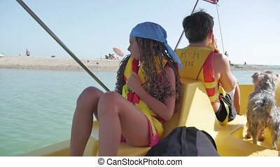 Happy family with a dog is swimming on a catamaran. Boy girl and woman on sea to the ocean. family holiday