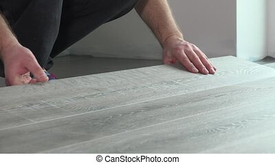 Contractor installing wooden laminate flooring with...