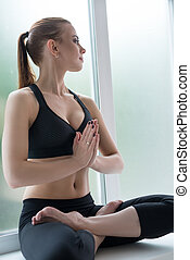 Young model on the window sill in yoga pose