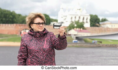 Adult woman aged 60s takes photos using smartphone