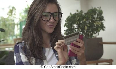 Woman holding a credit card and using cell phone for online shopping.