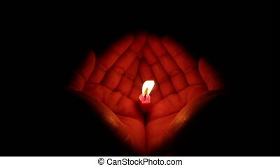 Candle In Hands On Black Background