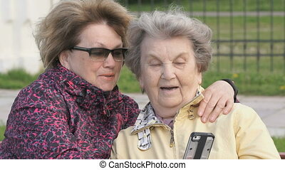 Woman shows photo to old woman using mobile phone - Two...