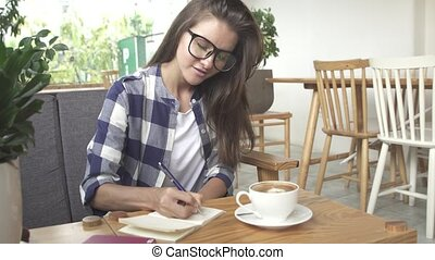 Stylish young girl writes in the journal in cafe - Stylish...