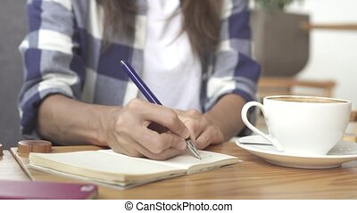 Close up of a Woman sitting and writing in her journal in...