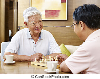 senior asian men playing chess