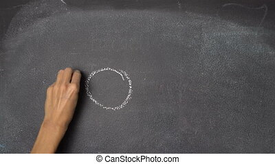 "Hand writing ""SUMMER"" and drawing sun on black chalkboard -..."