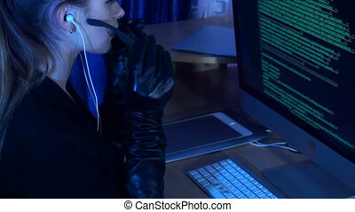 young woman hacker working with computer in dark office