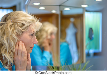 Middle-aged woman looking at herself in a mirror with her...
