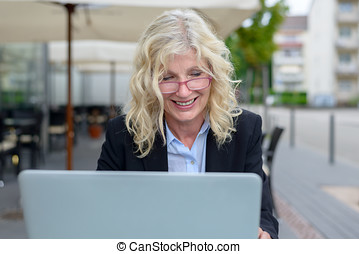 Middle-aged businesswoman working on her laptop -...