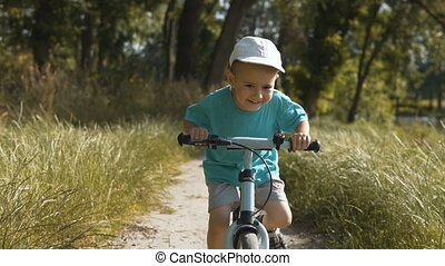 Kid Riding a Bike - Little kid boy wearing white cap riding...