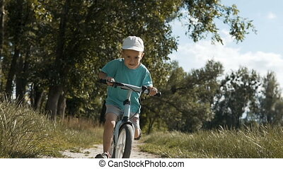 Kid Riding a Bike - Little kid boy wearing white cap riding...
