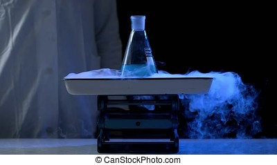 Bottle and liquid nitrogen in a laboratory. Chemical experiment. Flask with water and dry ice boiling chemical experiment