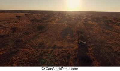 Tourists traveling by jeep across the savannah in Namibia. A...