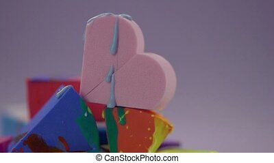 Blue paint drips onto a pink sponge in the shape of a heart.