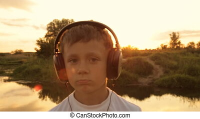 Boy listening to music through headphones in the nature under the sunset