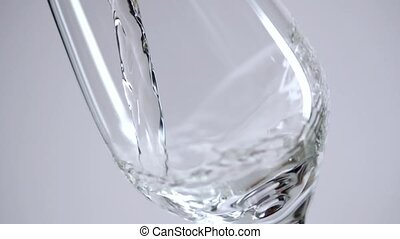 A portrait of a glass in which water begins to pour.