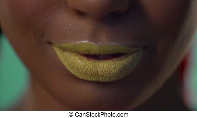 Smile of a swarthy woman with yellow lipstick on her lips.