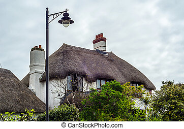 Interesting structure of roofs of rural buildings, roofs covered with straw, street lamp, buildings styled for medieval houses