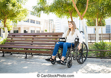Thoughtful woman using a wheelchair - Wide view of a young...
