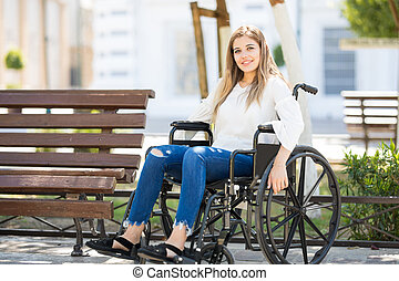 Cute young woman on a wheelchair