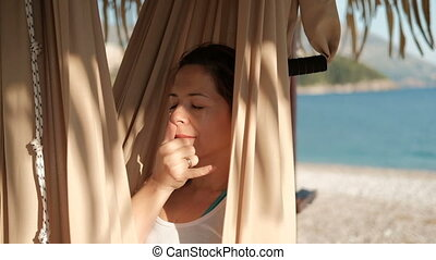 Woman in a hammock on the beach yoga breathing alternate...