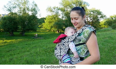 Woman with baby in nature. Mom walks with the baby in the...