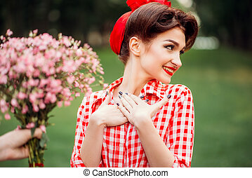 Glamour pinup girl takes gift a bouquet of flowers, retro...