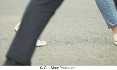 Crowd of people walking on the street - Detail of legs and shoes moving on sidewalk in city center. People walking on big city street, blurred motion crossing leg. Abstract