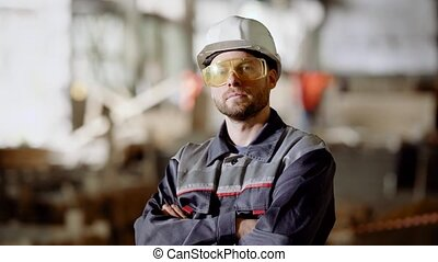 Close up of working man in uniform, protective hardhat and...