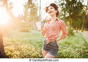 Pin up girl holds cardboard cup with a straw, city park on...