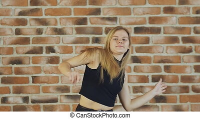Hip hop blonde girl dancing in modern style over urban brick wall. Slow motion.
