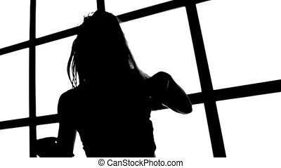 Silhouette of girl with long waving hair in profil on white background with grid window.
